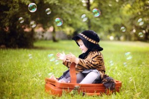 http://www.dreamstime.com/stock-image-little-cute-girl-hat-cloak-sitting-suitcase-image29645901