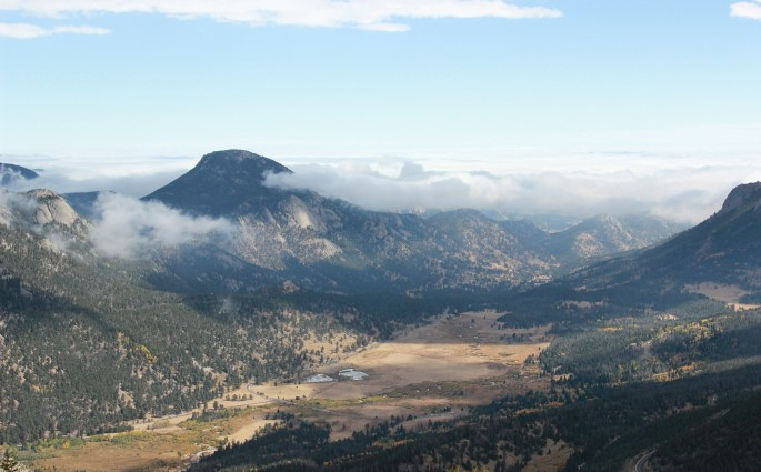 One of the lookout points in Rocky Mountain National Park overlooks a large valley, a small river system, a lake, and mountains.