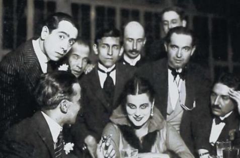 Abraham Valdelomar (en primer plano), José Carlos Mariátegui (con corbata negra ancha) y demás intelectuales de la época rodean a la bailarina Norka Rouskaya en el Palais Concert. Crédito de la foto: Archivo José Carlos Mariátegui.