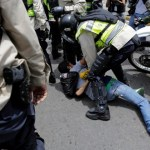 Riot police officers detain a demonstrator during clashes with opposition supporters in a rally to demand a referendum to remove President Nicolas Maduro in Caracas