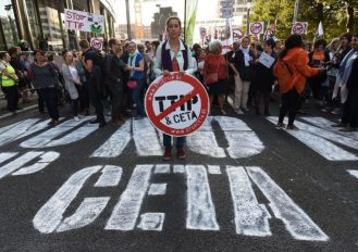 A woman holds a placard depicting a no entry sign with the TTIP and CETA logos, during a demonstration outside the European Union headquarters in Brussels, on September 20, 2016 to protest against huge transatlantic trade deals linking Europe with Canada and the United States. Several thousand  The protests came after mass rallies in German cities on September 17, 2016 against the European Union's planned Transatlantic Trade and Investment Partnership (TTIP) with the United States, and the Comprehensive Economic and Trade Agreement (CETA) with Canada.  / AFP / JOHN THYS        (Photo credit should read JOHN THYS/AFP/Getty Images)
