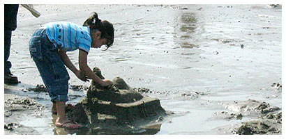 little girl with a sand castle