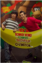 Takeru Kobayashi holds the Donkey Kong Country Returns Champion prize of an oversized banana with his challenger, a Donkey Kong fan. Photo Credit: PJ Stephen