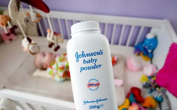C0JNP6 Bottle of Johnsons Baby Power talc  in front of a baby in a cot.. Image shot 02/2011. Exact date unknown.
