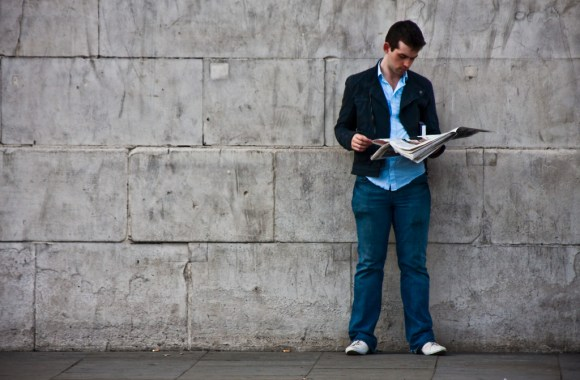Reading A Newspaper By A Wall