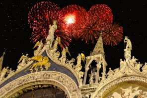 Detail of facade of Saint Mark's cathedral in Venice, Italy with Holiday fireworks exploding in the background.