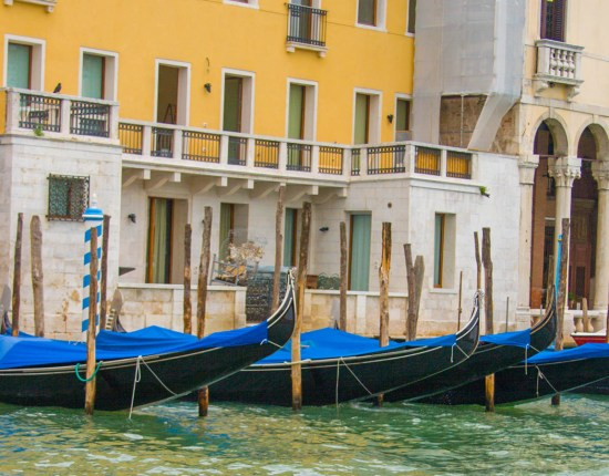 Venetial gondolas covered in blue sit docked against a yellow building