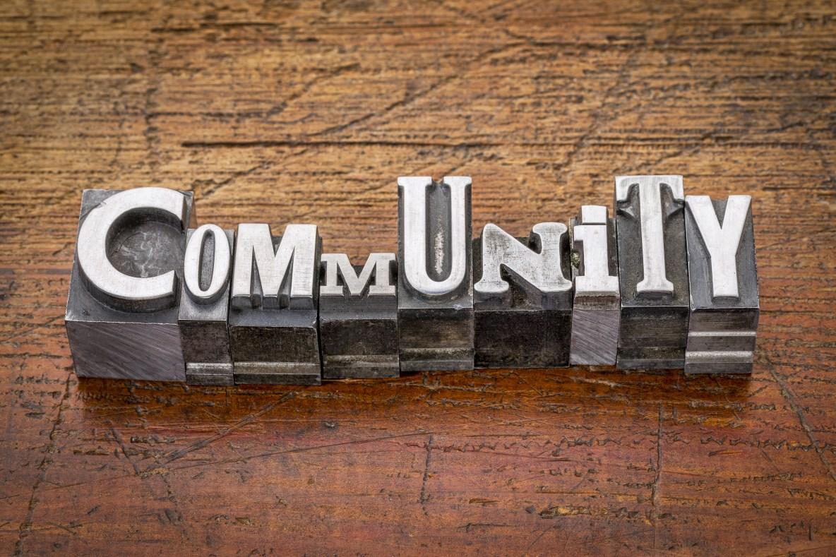 community  word in mixed vintage metal type printing blocks over grunge wood