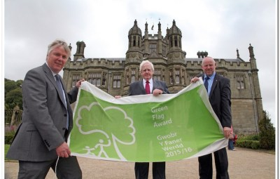 Margam Park Manager Michael Wynne, Neath Port Talbot Council Leader Cllr. Ali Thomas OBE and Margam Councillor Cllr. Rob Jones unveil the Green Flag in front of Margam Castle.