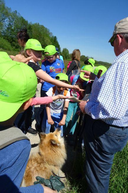 Hundebesitzer, Hund und Schüler freuen sich über die Begegnung und den Erfahrungsaustausch.