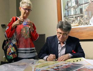 "Artist Mitch Markovitz signs copies of his ""Let's Go Hawks"" South Shore Line poster at the Center for Visual and Performing Arts in Munster."