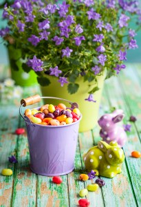 Easter rabbits and bucket with jelly beans on the vintage wooden table