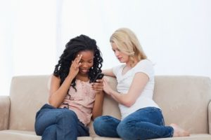 Two women sitting on a couch are looking at a mobile phone