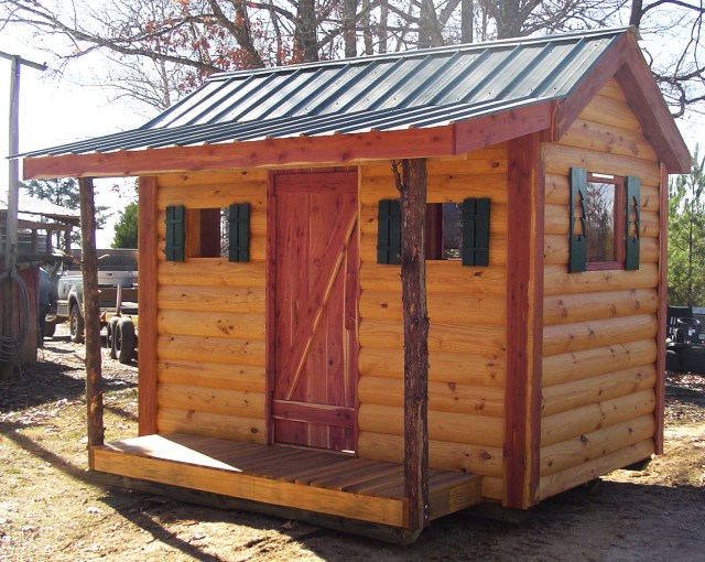 "The Patrick family makes log cabin siding with their Woodmaster Molder/Planer. This ""kid's cabin"" is a display unit they built to show the quality of their siding. The cabin gets people's attention and helps the Patricks sell log cabin siding."