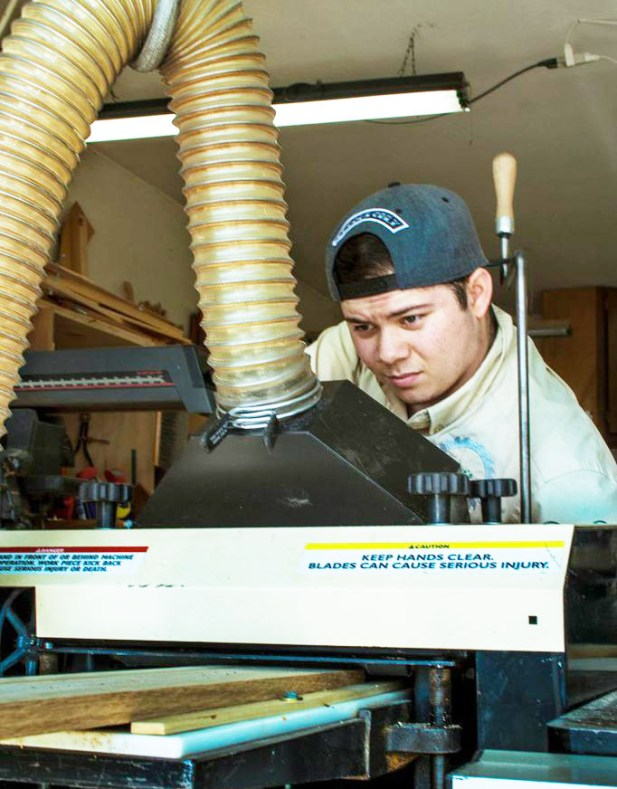 Colby keeps an eagle eye on molding he's about to run through Dave's Woodmaster Molder/Planer.