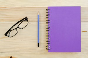 Purple Notebook with pencil and glasses on wooden table