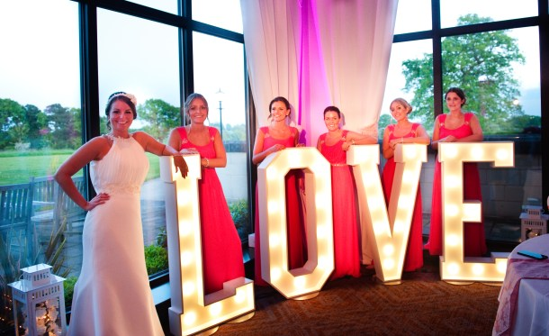 A bride and her five bridesmaids pictured with large LOVE wedding letters