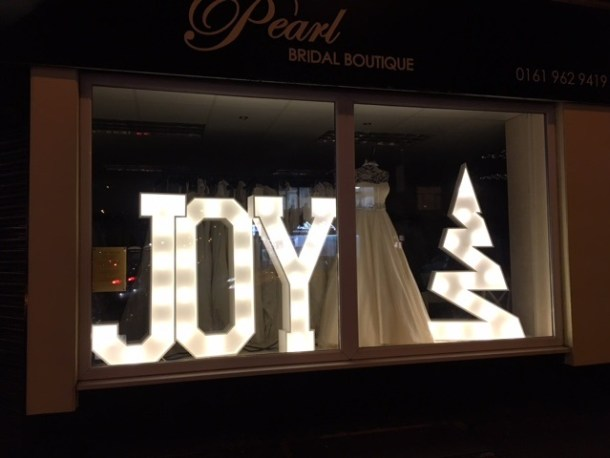 Bridal Shop Window Illuminated Letters spelling JOY and light up Christmas Tree