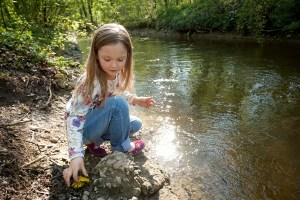 tossing stones into the creek English Garden Munich - @World Travel Mama