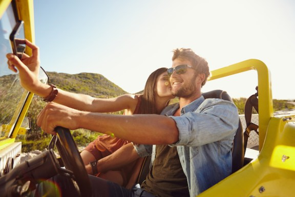 Woman kissing man and taking selfie on her mobile phone. Couple on road trip, man driving a buggy car on a summer day.