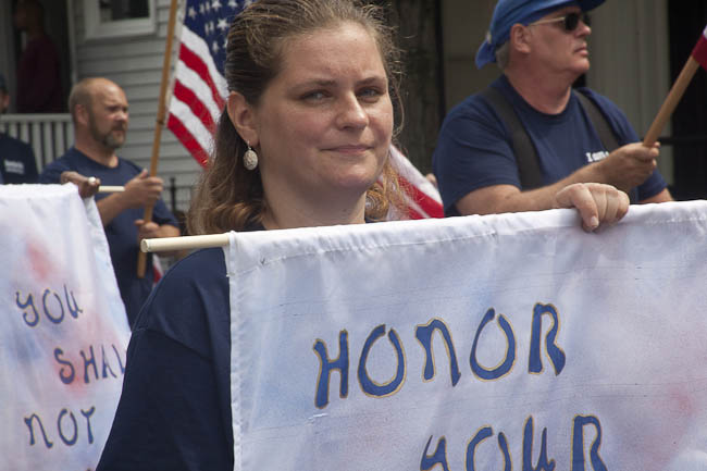 "woman with biblical ""honor"" banner"