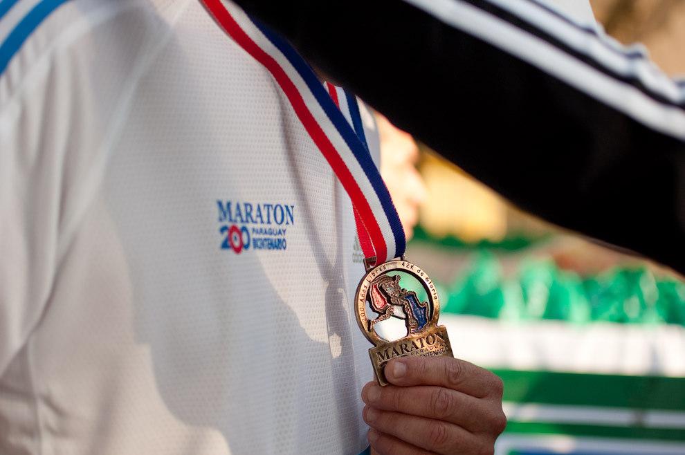 Un Atleta recibe su galardón de participación por parte de las chicas promotoras de la marca Adidas.   (Elton Núñez - Asunción, Paraguay)