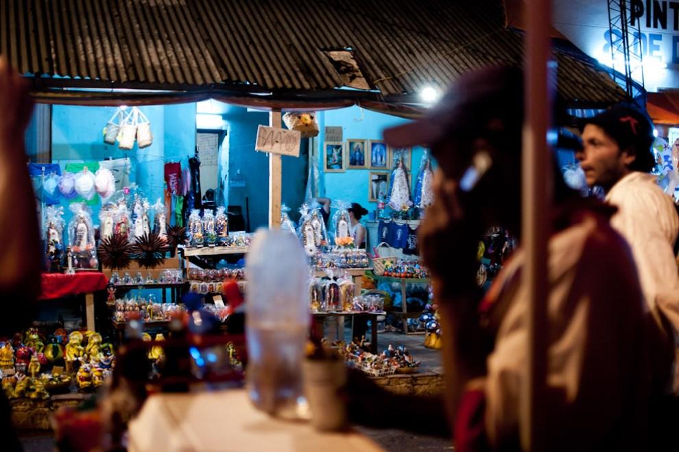 Un vendedor ambulante habla por celular frente a miles de imágenes de la Virgen de Caacupé que son vendidas como recuerdos en las aceras de la Ciudad cerca de la Basílica. (Elton Núñez - Caacupé, Paraguay)