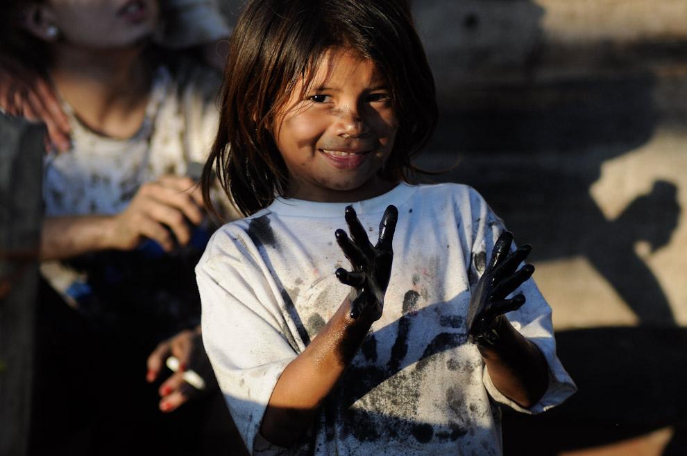 """Una niña con las manos manchadas de pintura aislante ayuda con la tarea de impermeabilizar la madera que será utilizada para construir su nueva casita mientras los chicos de """"Un techo para mi país"""" estaban preparando los cimientos. (Elton Núñez - Asunción, Paraguay)"""