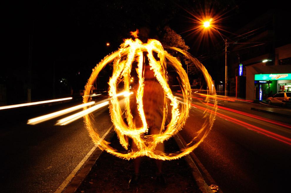 Pipi, un malabarista, entretiene al público con sus habilidades con 3 antorchas encendidas, sobre el paseo central de la Avenida Sacramento. (Elton Núñez - Asunción, Paraguay)