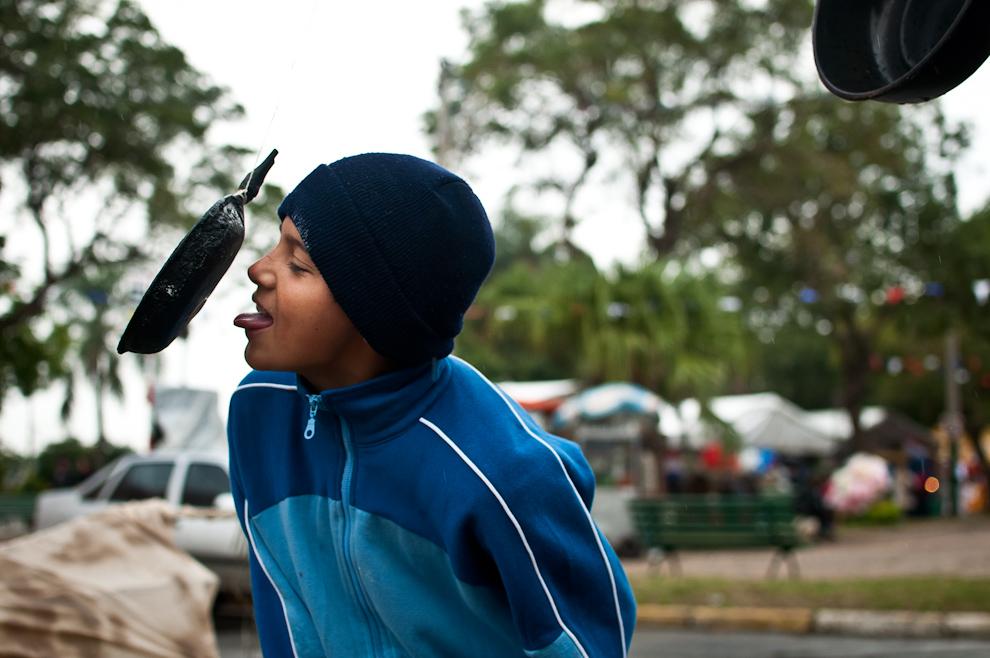 Un niño juega a la 'Paila Jeherei', un juego tradicional de las fiestas de San Juan en Junio, consiste en obtener una moneda pegada con grasa a una sartén, utilizando solamente la lengua. La foto corresponde a las celebraciones de San Juan en las plazas principales del Cabildo en Asunción. (Elton Núñez)
