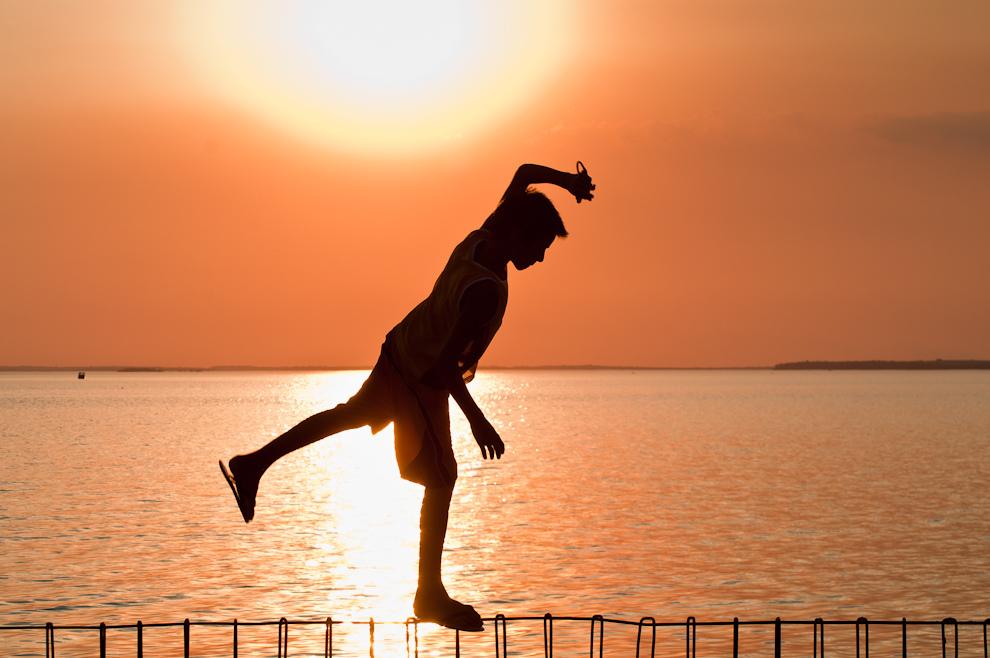"""Un travieso niño camina sobre lo que sería la estructura de metal de un muro de contención sin terminar, en la playa """"San José"""" de la costanera de Encarnación en la víspera de la semana santa, en horas de la tarde. (Elton Núñez)"""