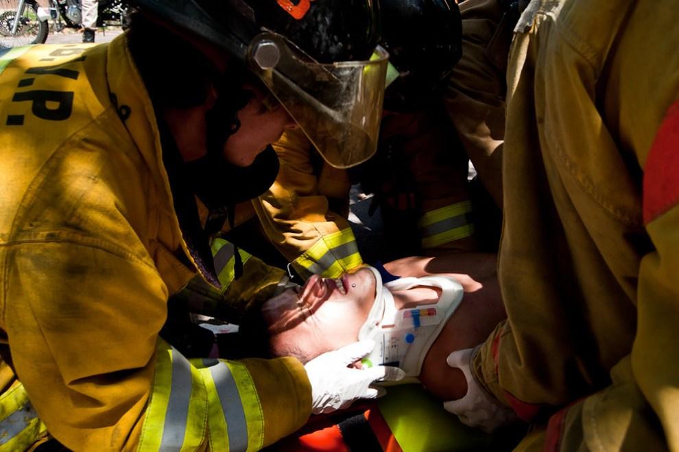 En la segunda entrega del fotoreportaje sobre los bomberos: Un bombero voluntario estabiliza la cabeza de una víctima de accidente en motocicleta mientras sus camaradas lo depositan en una camilla para ser trasladado a un hospital cercano, el accidente se produjo en la zona cerca de la Armada Nacional en Sajonia el pasado 4 de marzo durante el mediodía. La víctima sufrió severos daños y la pronta intervención de los bomberos ayudó a que fuese atendido en el hospital a tiempo antes que se produzcan efectos dañinos a consecuencia de golpes internos. (Elton Núñez).