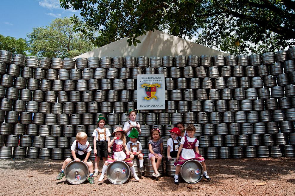 Niños vestidos con los trajes típicos de Alemania aposan para la foto al término de la Fiesta de la Cerveza más tradicional del Sur del Paraguay, frente al Club Alemán de Colonia Obligado se erigió un gran muro de barriles de cerveza consumidos durante la noche anterior. (Elton Núñez)