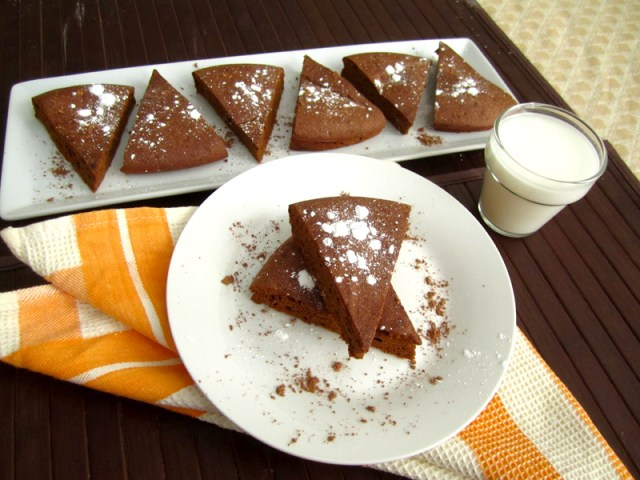 Side view of sliced brownies on plates with glass of milk
