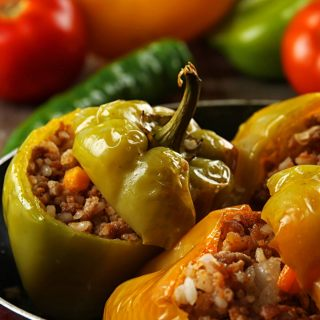 The sweetness of the peppers, the slightly spicy filling, the thick, rich tomato gravy, and a mound of fluffy mashed potatoes - I tell you, Croatian stuffed peppers are Heaven on a plate! | yumsome.com