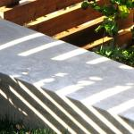 Resting at the garden's north end is a concrete bench that intersects the slatted wood fencing