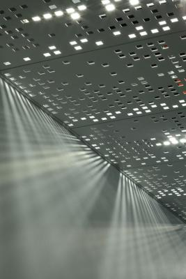 A custom perforated metal ceiling tile was developed and implemented to create a cinematic play of light.