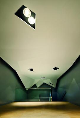 Corridor of EspaiCaixa. The coloured glass walls and the false ceiling give the building a unity, Image Courtesy © Jordi Surroca