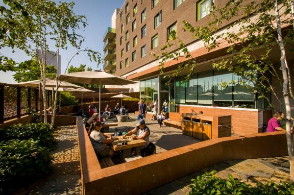 Bud Clark Commons' public courtyard, sheltered from the traffic and street, provides a safe and dignified place for homeless individuals seeking services to wait, socialize, and experience nature within an urban environment. - Photo Credit: Bruce Forster