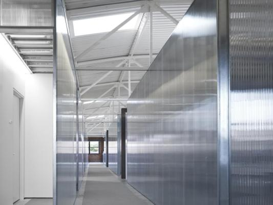 The 2nd floor workspace corridor is asymmetrically placed in order to take advantage of the existing skylight locations.  The polycarbonate is transparent,reflective and private all at once., Image Courtesy ©  Scott McDonald, Hedrich Blessing