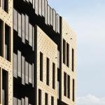 Building façade – the irregular metal mesh fields wraps the regular bricks fields, Image Courtesy © Miran Kambič