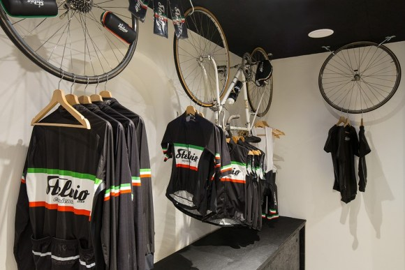 In the store the uniforms for cyclists are exposed characteristically, Image Courtesy © Bellotti Enrico Architects