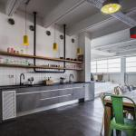 kitchen with industrial pipes hanging upper shelves, Image Courtesy © Yoav Gurin
