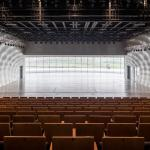 Panoramic window backdrops the small theater stage with the surrounding landscape, Image Courtesy © Adam Mørk
