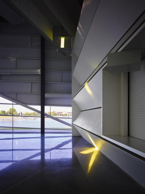 """Performance Hall looking west with acoustical sound trap wall on right.  The polished concrete floor connects the inside to the river outside.  One gold glass """"note"""" is visible.  """"Notes"""" appear, move, change and disappear during the day capturing the kinetic energy within the space, Image Courtesy © Gray City Studios (Scott McDonald)"""
