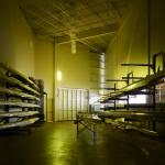 """The Boat Storage Room is lighted as if the space is a pinhole camera.  One gold  """"note"""" illuminates the entire space. """"Notes"""" appear, move, change and disappear during the day capturing the kinetic energy within the space, Image Courtesy © Gray City Studios (Scott McDonald)"""