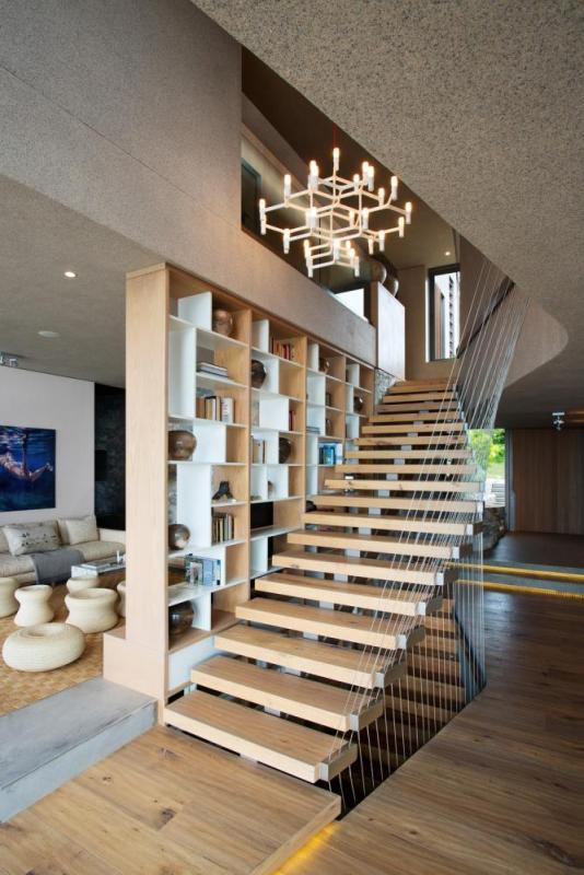 A floating staircase acts as a partition between the dining area and the TV room, Image Courtesy © Adam Letch