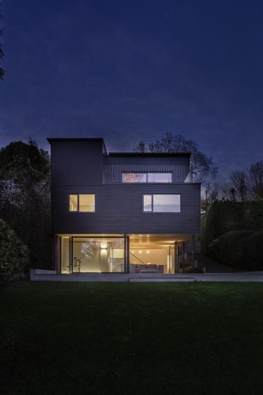 The dark cladded façade provides a dramatic contrast to the warmth inside the house, Image Courtesy © Martin Gardner