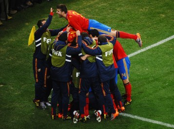 Gerard Pique of Spain jumps on top of his team mates as they celebrate David Villa scoring the opening goal during the 2010 FIFA World Cup South Africa Round of Sixteen match between Spain and Portugal at Green Point Stadium on June 29, 2010 in Cape Town, South Africa.