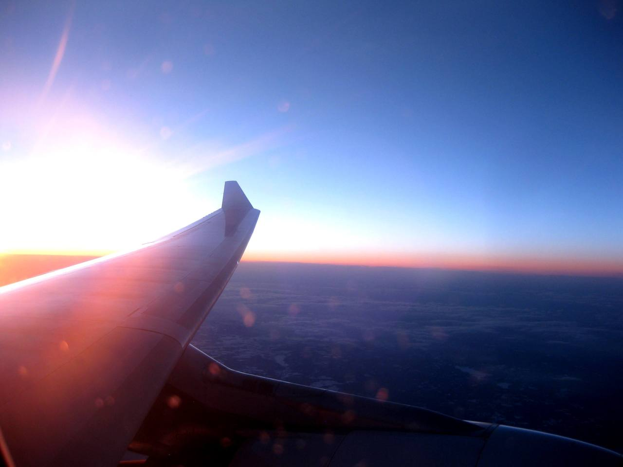 Staring out an aeroplane window into the sunset.